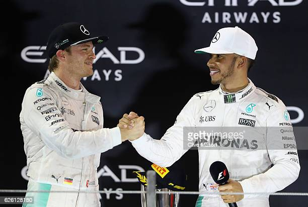 Race winner Lewis Hamilton of Great Britain and Mercedes GP shakes hands with second place finisher and F1 World Drivers Champion Nico Rosberg of...