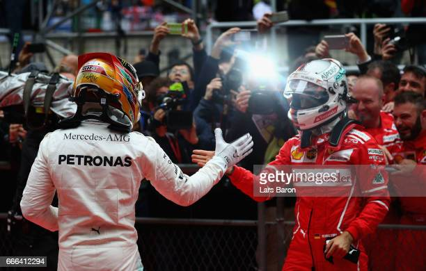Race winner Lewis Hamilton of Great Britain and Mercedes GP shakes hands with second placed finisher Sebastian Vettel of Germany and Ferrari in parc...