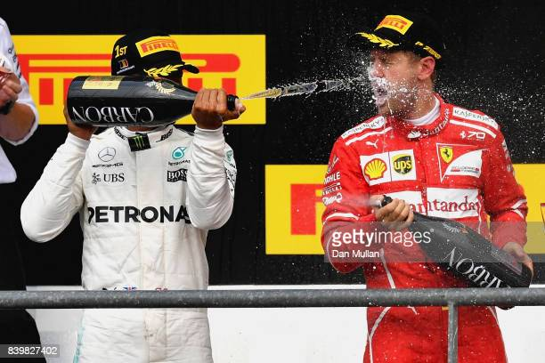 Race winner Lewis Hamilton of Great Britain and Mercedes GP celebrates with second placed Sebastian Vettel of Germany and Ferrari during the Formula...