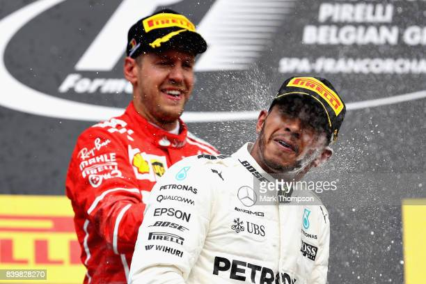 Race winner Lewis Hamilton of Great Britain and Mercedes GP celebrates with second placed Sebastian Vettel of Germany and Ferrari on the podium...