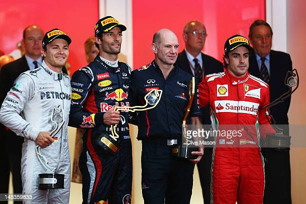 Race winner Mark Webber of Australia and Red Bull Racing celebrates on the podium with second placed Nico Rosberg of Germany and Mercedes GP third...