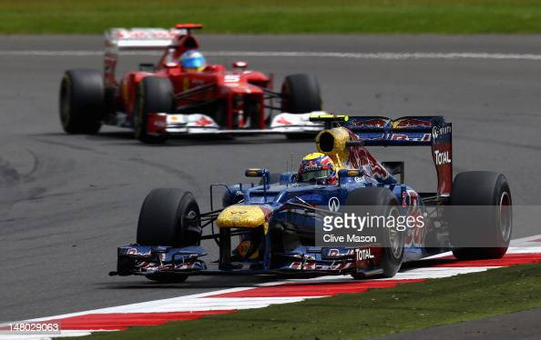 Race winner Mark Webber of Australia and Red Bull Racing leads from second placed Fernando Alonso of Spain and Ferrari during the British Grand Prix...