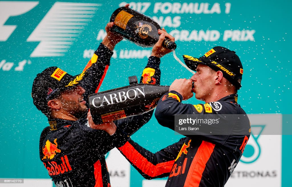 Race winner Max Verstappen of Netherlands and Red Bull Racing celebrates with third place finisher Daniel Ricciardo of Australia and Red Bull Racing on the podium during the Malaysia Formula One Grand Prix at Sepang Circuit on October 1, 2017 in Kuala Lumpur, Malaysia.