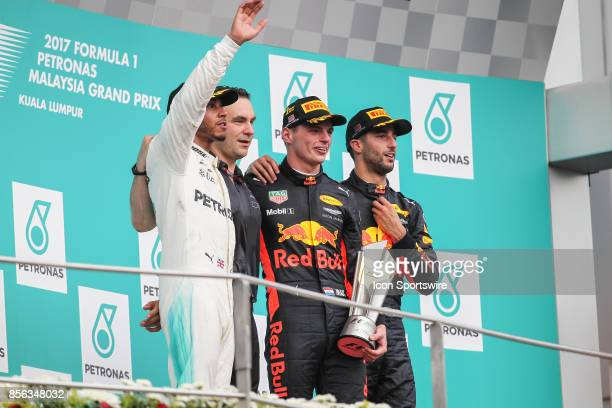 Race winner Max Verstappen of Red Bull Racing celebrates with second place finisher Lewis Hamilton and Mercedes GP third place finisher Daniel...