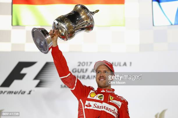 Race winner Sebastian Vettel of Germany and Ferrari celebrates his win on the podium during the Bahrain Formula One Grand Prix at Bahrain...