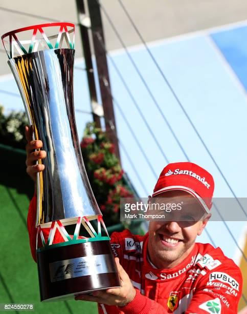 Race winner Sebastian Vettel of Germany and Ferrari celebrates on the podium during the Formula One Grand Prix of Hungary at Hungaroring on July 30...