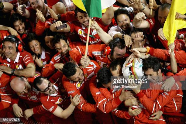 Race winner Sebastian Vettel of Germany and Ferrari celebrates with his team in parc ferme during the Bahrain Formula One Grand Prix at Bahrain...