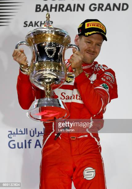 Race winner Sebastian Vettel of Germany and Ferrari celebrates with his trophy on the podium during the Bahrain Formula One Grand Prix at Bahrain...