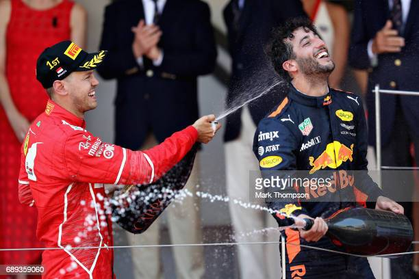 Race winner Sebastian Vettel of Germany and Ferrari celebrates with third place finished Daniel Ricciardo of Australia and Red Bull Racing on the...