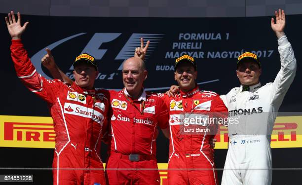 Race winner Sebastian Vettel of Germany and Ferrari celebrates with second place Kimi Raikkonen of Finland and Ferrari third place Valtteri Bottas of...