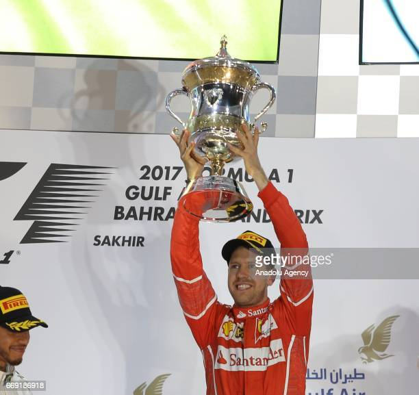Race winner Sebastian Vettel of Germany and Ferrari holds the trophy after getting first place at the Bahrain Formula One Grand Prix a threeway...