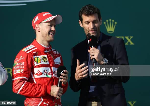 Race winner Sebastian Vettel of Germany and Ferrari talks with Mark Webber on the podium during the Australian Formula One Grand Prix at Albert Park...