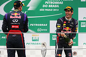 Race winner Sebastian Vettel of Germany and Infiniti Red Bull Racing celebrates on the podium with second placed team mate Mark Webber of Australia...
