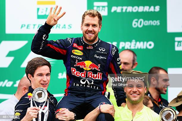 Race winner Sebastian Vettel of Germany and Infiniti Red Bull Racing celebrates on the podium with team mates following the Brazilian Formula One...