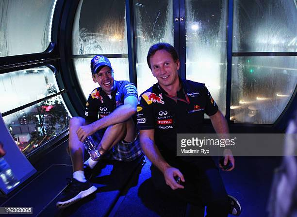 Race winner Sebastian Vettel of Germany and Red Bull Racing and his Team Principal Christian Horner ride the Singapore Flyer big wheel following the...