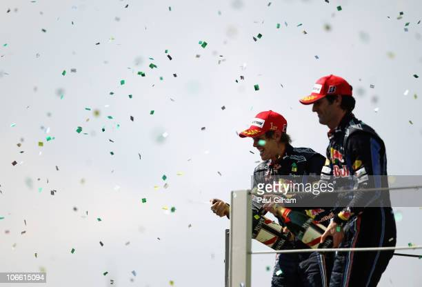 Race winner Sebastian Vettel of Germany and Red Bull Racing and second placed Mark Webber of Australia and Red Bull Racing celebrate on the podium as...