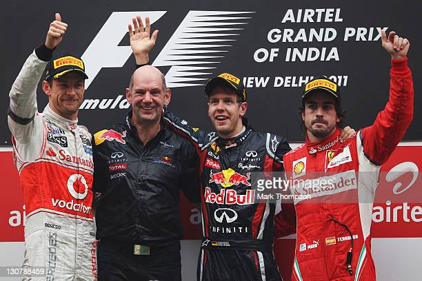 Race winner Sebastian Vettel of Germany and Red Bull Racing celebrates on the podium with Red Bull Racing Chief Technical Officer Adrian Newey second...