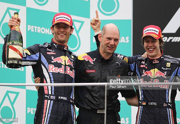 Race winner Sebastian Vettel of Germany and Red Bull Racing celebrates on the podium with second placed team mate Mark Webber of Australia and Red...