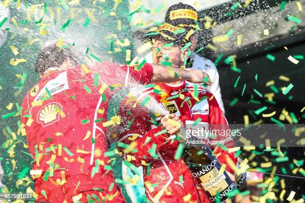 Race winner Sebastian Vettel of Germany driving for Scuderia Ferrari sprays champagne as he is hugged by Ferrari's trackside engineering team member...