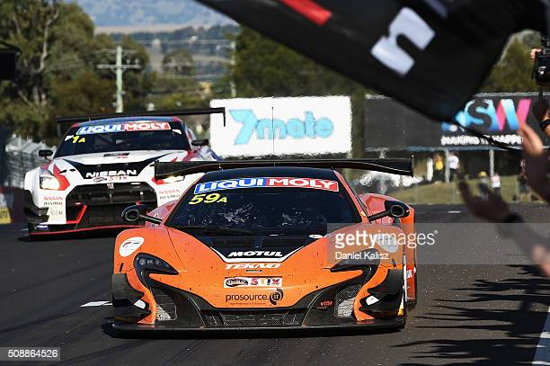 Race winner Shane van Gisbergen driver of the Tekno Autosport McLaren 650S crosses the finish line to win the Bathurst 12 Hour Race at Mount Panorama...