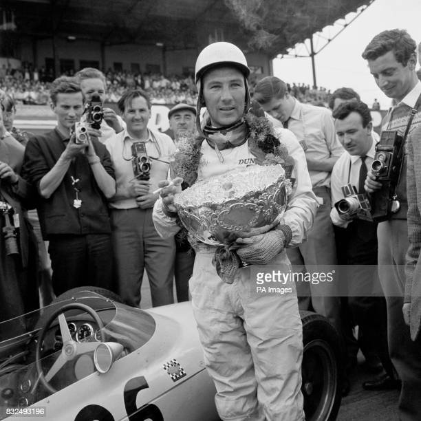 Race winner Stirling Moss is the centre of attention as he holds the trophy after his victory in the 200mile race during which he lapped all but the...