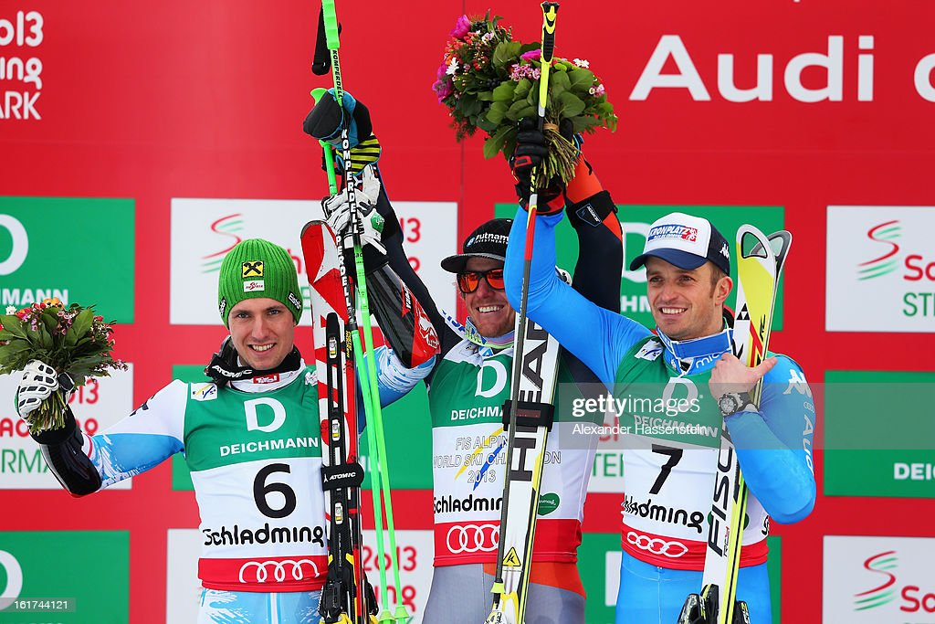 Race winner Ted Ligety (C) of the United States of America celebrates with second placed Marcel Hirscher (L) of Austria and third placed Manfred Moelgg (R) of Italy at the flower ceremony following the Men's Giant Slalom during the Alpine FIS Ski World Championships on February 15, 2013 in Schladming, Austria.