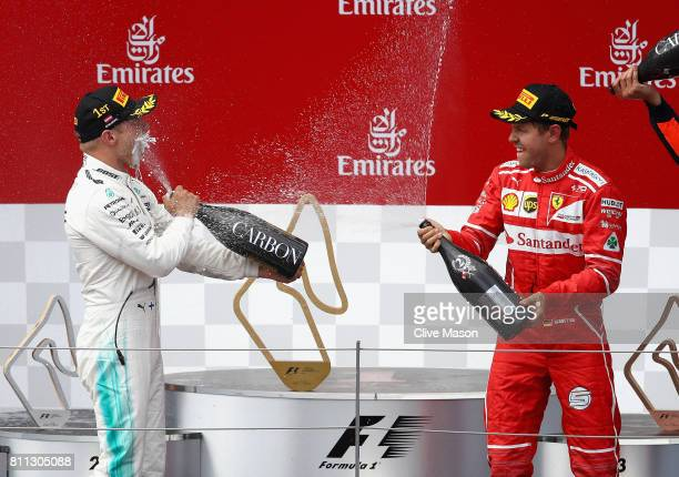 Race winner Valtteri Bottas of Finland and Mercedes GP and second placed Sebastian Vettel of Germany and Ferrari celebrate on the podium during the...