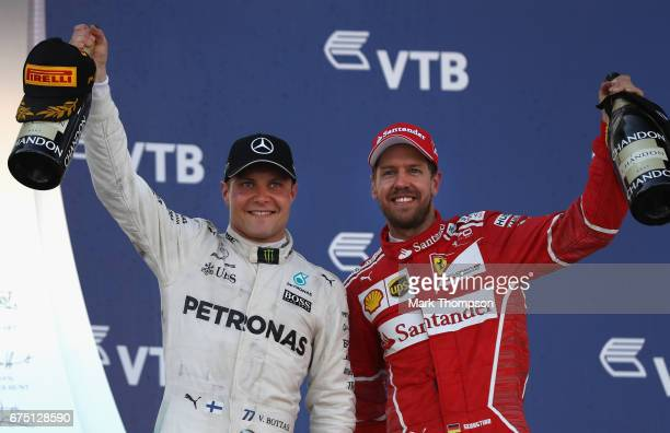 Race winner Valtteri Bottas of Finland and Mercedes GP celebrates with second placed finisher Sebastian Vettel of Germany and Ferrari on the podium...