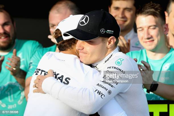 Race winner Valtteri Bottas of Finland and Mercedes GP is congratulated by team mate Lewis Hamilton of Great Britain and Mercedes GP during the...