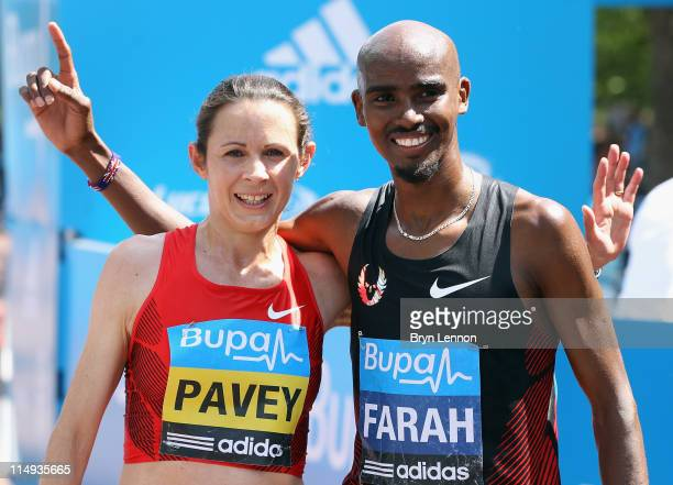 Race winners Jo Pavey and Mo Farah of Great Britain pose on the finishline after the Bupa London 10000 Run on May 30 2011 in London England