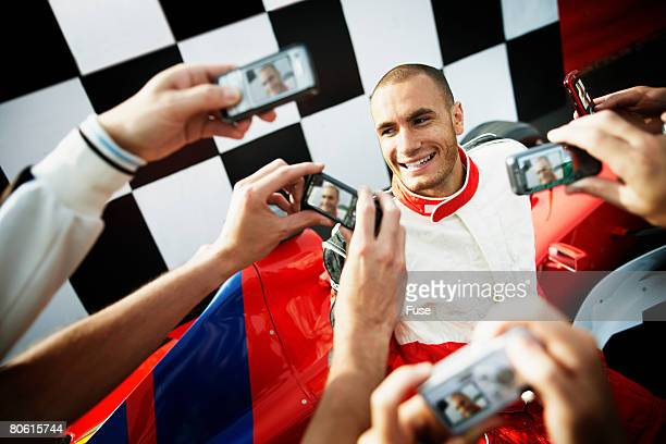Racecar Driver Being Photographed by Fans