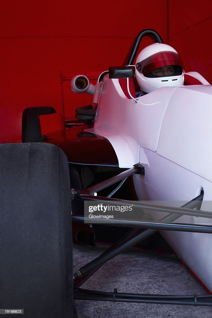 Racecar driver in a racecar under a shed : Foto de stock
