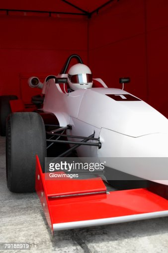 Racecar driver in a racecar under a shed : Stock Photo