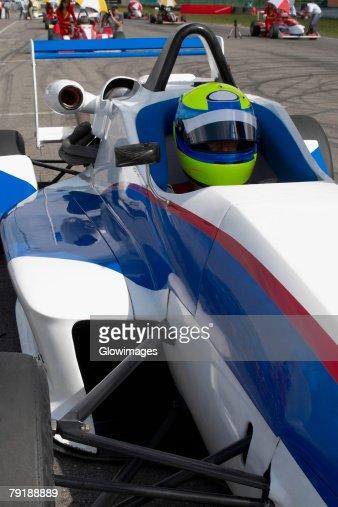 Racecar driver sitting in a racecar : Stock Photo