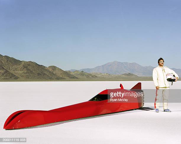 Racecar driver standing alongside streamliner car, portrait