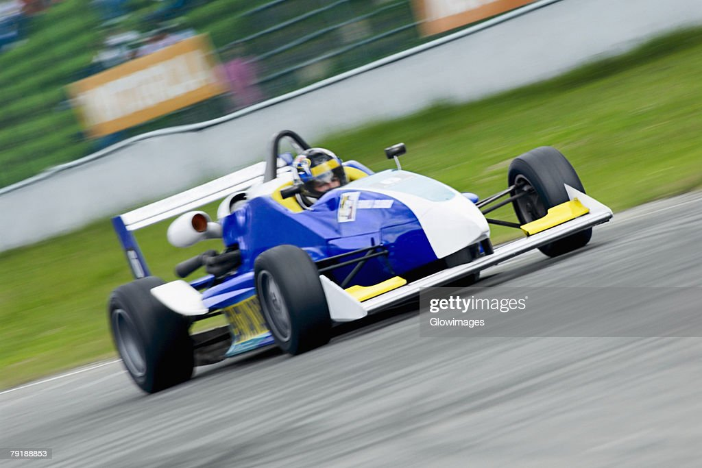 Racecar racing on a motor racing track : Stock Photo