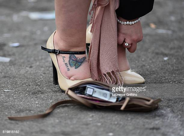 Racegoer adjusts her shoes during Ladies Day at Aintree Racecourse on April 8 2016 in Liverpool England