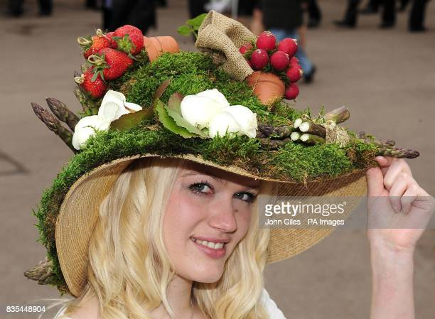 Racegoer Beth Ridley wears a hat decorated with garden produce including radish asparagus strawberries potatoes and roses at York Racecourse