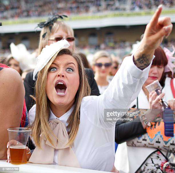 A racegoer cheers as she watches the racing on day 2 'Ladies Day' of the Crabbie's Grand National Festival at Aintree Racecourse on April 8 2016 in...