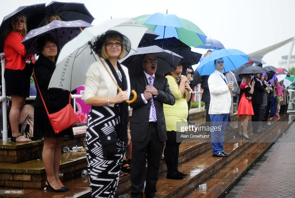 A racegoer cheers home a winner as heavy rain falls at Chester racecourse on May 08, 2014 in Chester, England.