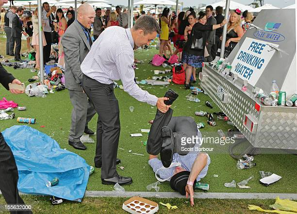 A racegoer falls over after the Melbourne Cup at Flemington Racecourse on November 6 2012 in Melbourne Australia