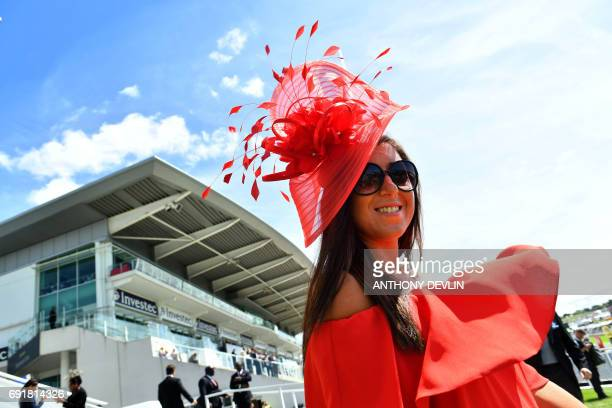 A racegoer gestures ahead of the Investec Derby at Epsom Downs Racecourse in Surrey on June 3 2017 / AFP PHOTO / Anthony Devlin