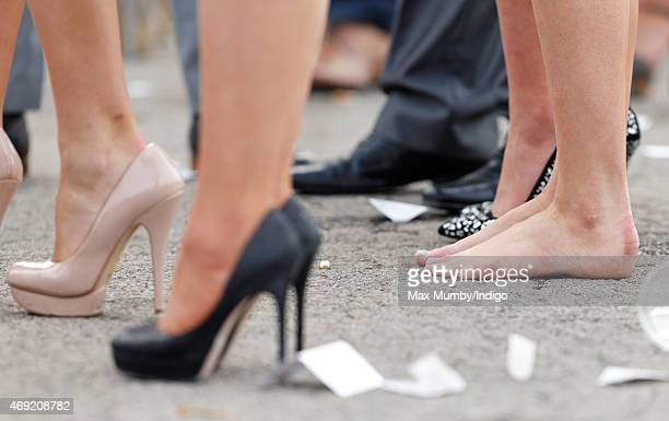 A racegoer goes barefoot as she attends day 2 'Ladies Day' of the Crabbie's Grand National Festival at Aintree Racecourse on April 10 2015 in...