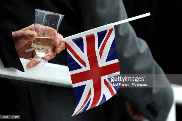 A racegoer holds a Union Flag and glass of white wine