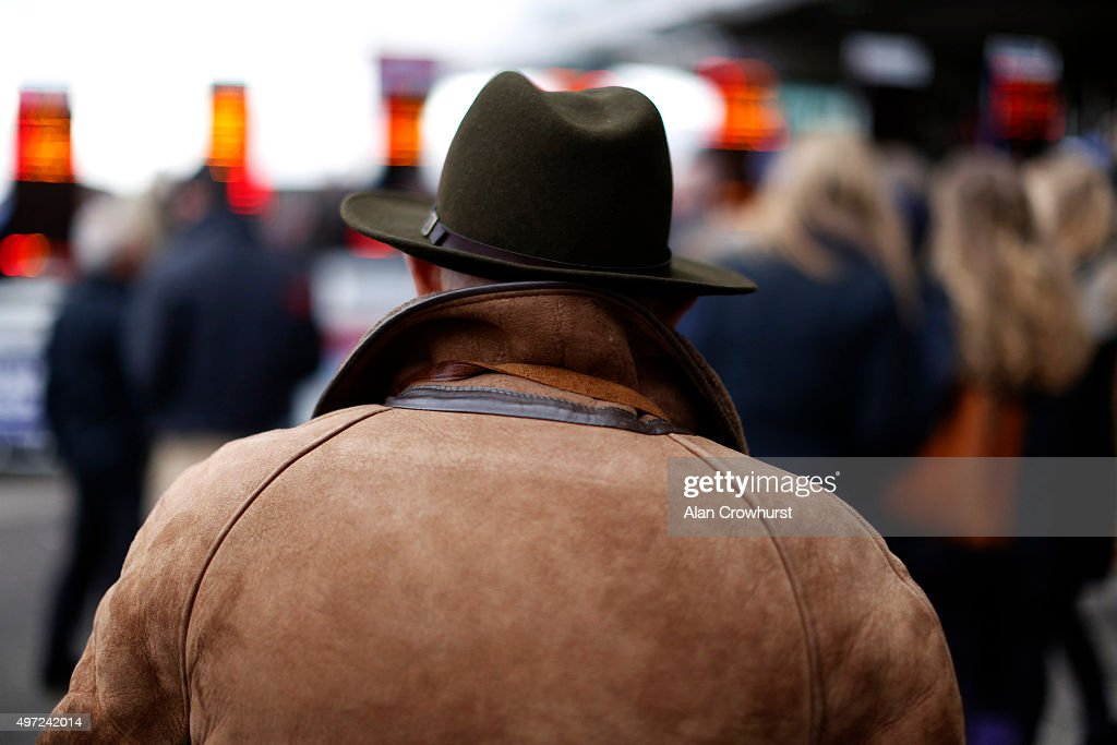A racegoer in a trilby hat and sheepskin coat checks out the bookmakers odds at Cheltenham racecourse on November 15 2015 in Cheltenham England