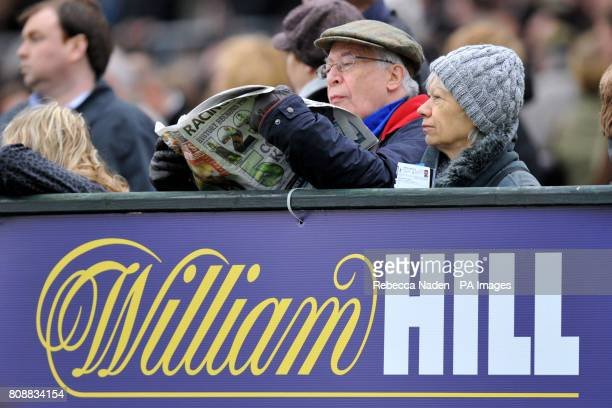 A racegoer inspects the Racing Post newspaper for tips