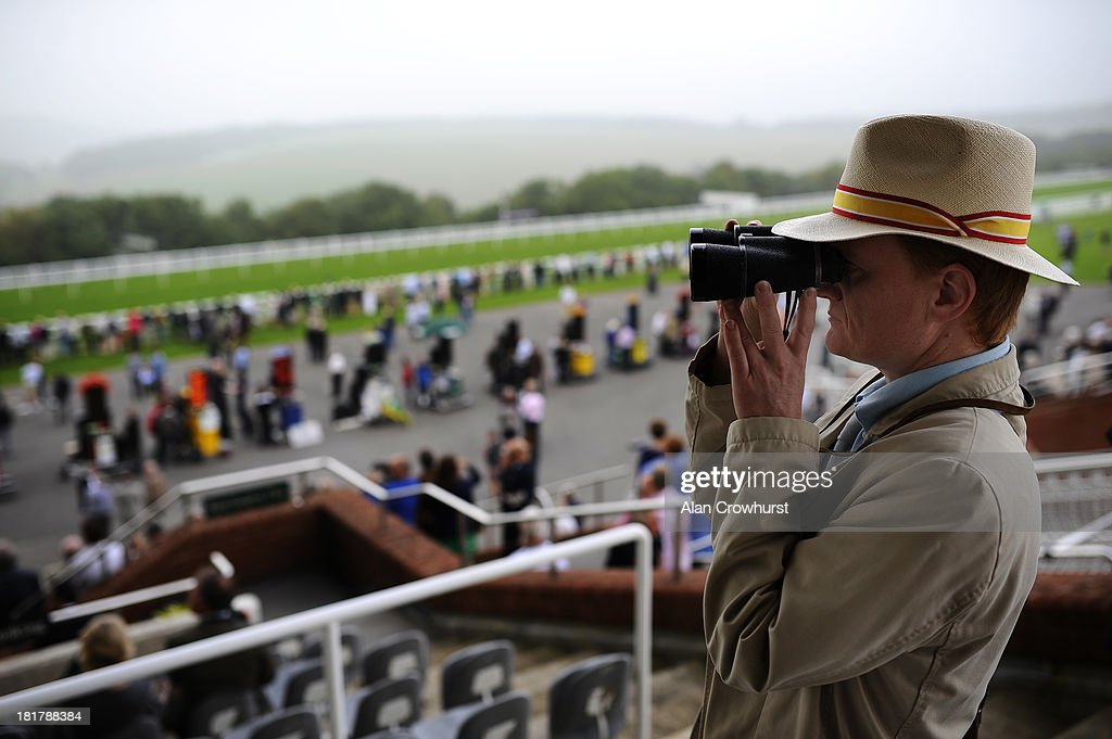 A racegoer keeps an eye on the action at Goodwood racecourse on September 25, 2013 in Chichester, England.