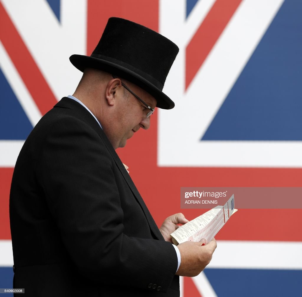 A racegoer looks at the racing schedule card during on the fourth day of Royal Ascot in Berkshire west of London on June 17 2016 The fiveday meeting...