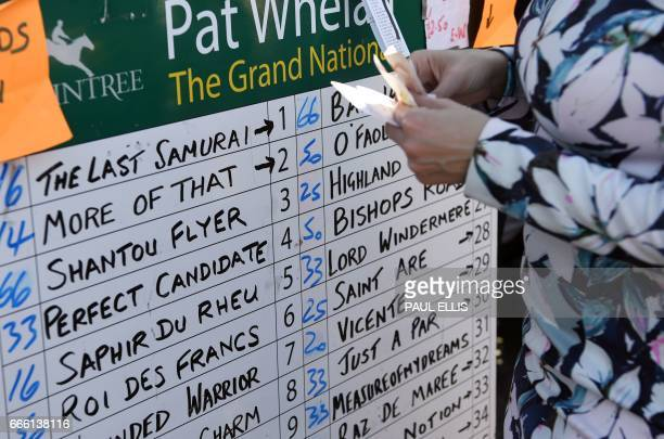 A racegoer places a bet with a bookmaker ahead of the first race of the final day of the Grand National Festival horse race meeting at Aintree...