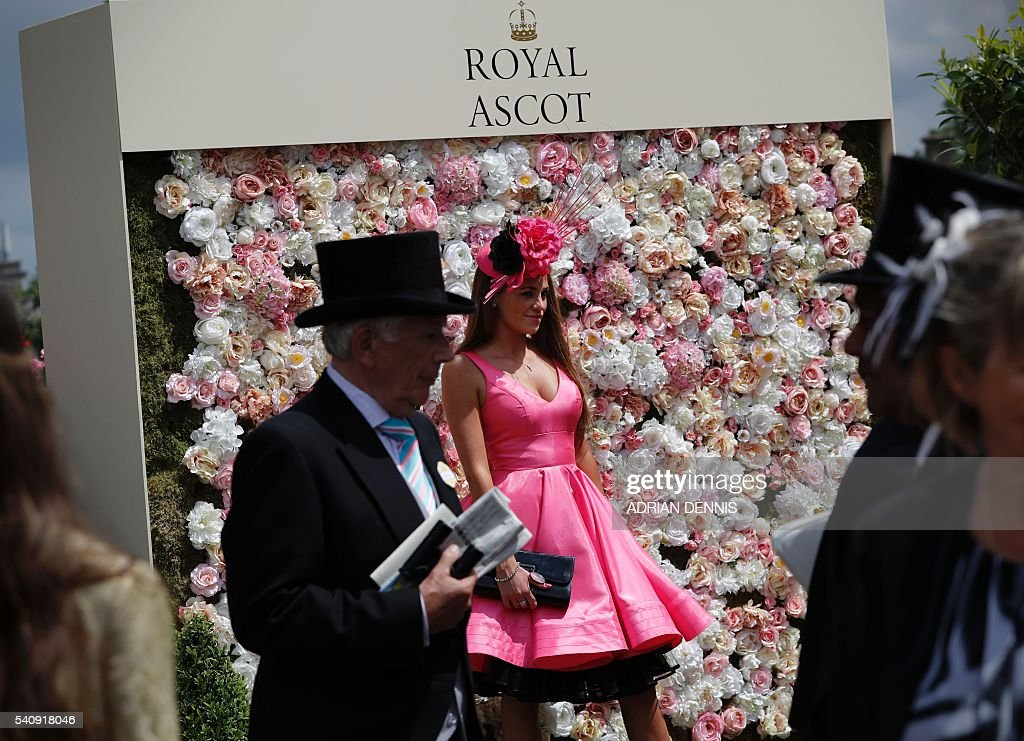 A racegoer poses for a photograph during day four at Royal Ascot horse racing meet in Ascot west of London on June 17 2016 The fiveday meeting is one...